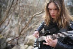 Vagga gitarristen på momenten En musiker med en elbas i a Royaltyfri Bild