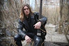 Vagga gitarristen på momenten En musiker med en elbas i a Royaltyfri Fotografi