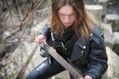 Vagga gitarristen på momenten En musiker med en elbas i a Arkivfoto