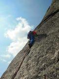 Vagga iklädda ljusa färger för klättraren på en brant granitklättringrutt i fjällängarna royaltyfri bild