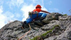 Vagga iklädda ljusa färger för klättraren på en brant granitklättringrutt i fjällängarna arkivfoto