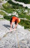 Vagga iklädda ljusa färger för klättraren på en brant granitklättringrutt i fjällängarna arkivbild