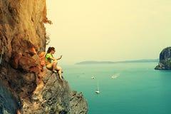 Vagga klättrarebrukssmartphonen på sjösidabergklippan arkivfoton