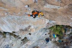 Vagga klättraren, den yrkesmässiga idrottsman nen som klättrar en brant klippa extrema sportar Royaltyfri Bild