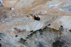 Vagga klättraren, den yrkesmässiga idrottsman nen som klättrar i bergen extrema sportar arkivbild