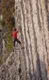 Vagga klättraren på klättringrutten för 6 kvalitet av den vertikala stenväggen arkivfoton