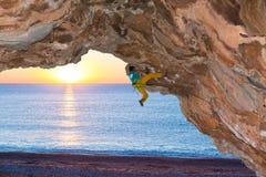 Vagga klättraren som anfaller det hängande över steniga taket på bakgrund för havsstrandsoluppgång Arkivbild