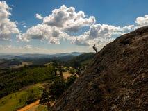 Vagga klättraren som konturn i ett brant vaggar med härligt landskap i bakgrunden i Brasilien arkivfoton