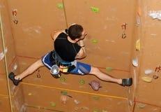 Vagga klättraren som rymmer splittringar, medan klättra den bruna väggen fotografering för bildbyråer