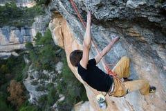 Vagga klättraren som stiger en utmanande klippa Extrem sportclimbi royaltyfri bild