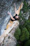 Vagga klättraren som stiger en utmanande klippa Extrem sportclimbi arkivfoto