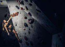 Vagga-klättring för sportswear för ung kvinna bärande övande på en vägg inomhus royaltyfria bilder