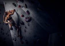 Vagga-klättring för sportswear för ung kvinna bärande övande på en vägg inomhus arkivbilder