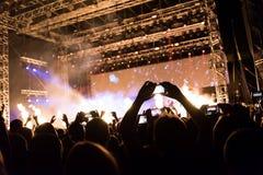 Vagga konserten, konturer av lyckligt folk som upp lyfter händer Arkivbild