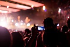 Vagga konserten med smartphonen Arkivfoton