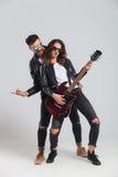 Vagga - och - rullar par som spelar den elektriska gitarren och skri Arkivbild