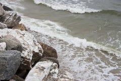 Vagga stranden och havet vinkar Arkivfoto