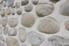 Vagga väggen av naturliga flodstenar Rund bakgrund för stenvägg Modell för flodrundastenar Små röda stenar Floden vaggar Arkivbilder