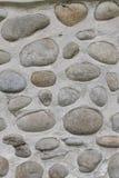 Vagga väggen av naturliga flodstenar Rund bakgrund för stenvägg Modell för flodrundastenar Små röda stenar Floden vaggar backgrou Royaltyfri Foto