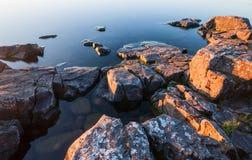 Vaggar av stenig kust i lugna vatten av sjön Arkivbilder
