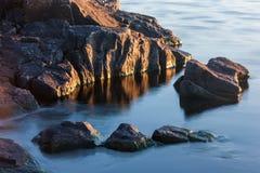 Vaggar av stenig kust i sjövatten Royaltyfria Bilder