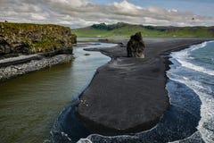 Vaggar bildande på Dyrholaey udde med den svarta sandstranden Arkivfoton