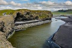 Vaggar bildande på Dyrholaey udde med den svarta sandstranden Royaltyfri Fotografi