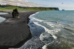 Vaggar bildande på Dyrholaey udde med den svarta sandstranden Royaltyfria Bilder