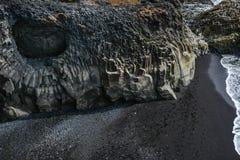 Vaggar bildande på Dyrholaey udde med den svarta sandstranden Arkivbild