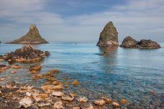 Vaggar den färgrika sikten för Aci Trezza Sicilien av cyclopean i det blåa havet och den steniga kusten arkivbilder