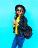 Vaggar den nätta unga le kvinnan för mode som använder smartphonen som bär en svart, stilkläder över färgrika blått Arkivbilder