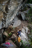 Vaggar förbereder sig bärande klättringutrustning för den unga mannen som står framme av en sten, utomhus- och att klättra, den b Royaltyfri Fotografi
