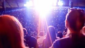 Vaggar hållande ögonen på och lyssnande musik för stor folkmassa på festival på stadiontribun Perfekt bakgrund för att illustrera arkivfoto