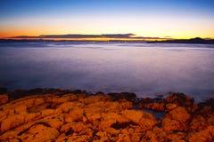 Vaggar i det dimmiga havet i solnedgång Royaltyfri Bild