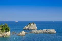 Vaggar i det Ionian havet med den lilla kyrkan och yacht i bakgrund - Parga, Grekland Royaltyfri Foto