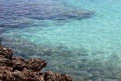 Vaggar och det blåa cristal havet royaltyfria bilder