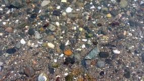 Vaggar och kiselstenar i havet Arkivfoto
