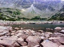Vaggar och stenar på en sjöstrand för det höga berget arkivbilder