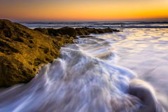 Vaggar och vinkar i Atlanticet Ocean på soluppgång gömma i handflatan in kusten, Royaltyfri Bild