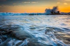 Vaggar och vinkar i Stilla havet på solnedgången Royaltyfri Foto