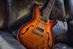 ` Vaggar på den halva hollowbody akustiska elektriska gitarren för `-tappning i läderstol med hackan Royaltyfri Bild