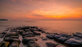 Vaggar på stenstranden på solnedgången Härlig strandsolnedgånghimmel Skymninghav och himmel tropiskt skymninghav clouds den drama arkivbilder
