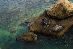 Vaggar sitta för två lokalt pojkar omgivet vatten annat Arkivbilder