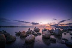 Vaggar stranden i aftonen med solnedgånghimmelbakgrunder Arkivfoto