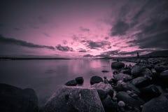 Vaggar stranden i aftonen med svartvita bakgrunder Fotografering för Bildbyråer