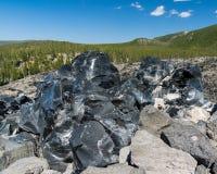 Vaggar svart vulkaniskt för Obsidian exponeringsglas Fotografering för Bildbyråer