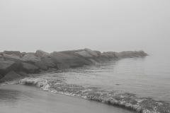 Vaggar vid stranden på en dimmig dag - lagerföra fotoet Royaltyfri Bild