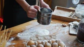 Vagliare farina al il setaccio Mani delle donne che vagliano farina su una tavola Cucinando ed appoggiando preparazione archivi video