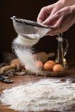 Vagliare farina da un filtro su una tavola di legno Fotografie Stock