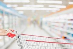 Vagn för shopping för kvinnahandhåll med suddighetssupermarketbakgrund arkivbild
